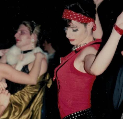 Frau mit rotem T-Shirt und rotem Haarband tanzt auf einem der ersten Tuntenbälle